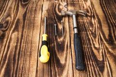 Młoteczkowy gwóźdź, śruba i śrubokręt na drewnianym tle, zdjęcia stock