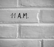 11 A M 写在白色简单的砖墙 免版税库存图片