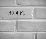 10 a M 写在白色简单的砖墙 免版税库存图片