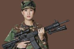 美丽的年轻人美国陆战队战士画象有M4攻击步枪的在棕色背景 库存图片