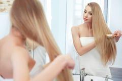 头发 美丽白肤金发掠过她的头发 护发 温泉秀丽M 免版税库存图片