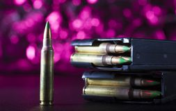 AR-15 magazines and ammo with a purple background. M855 ammunition with two metal magazines and purple behind Stock Photo