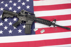 M4A1 carbine with blank dog tags on us flag Stock Photos