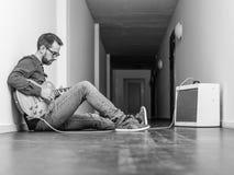 Mężczyzna bawić się gitarę elektryczną w korytarzu obrazy royalty free
