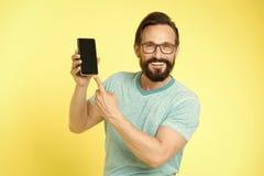 M??czyzna excited o nowych mobilnych sposobno?ciach Facet?w eyeglasses rozochocony wskazywa? przy smartphone M??czyzna u?ytkownik zdjęcie stock
