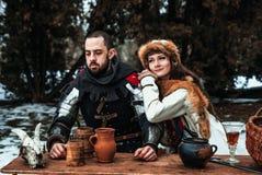 Mężczyzna i kobieta w dziejowych kostiumach siedzimy przy stołem zdjęcie royalty free