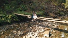 M??czyzna i kobieta w mi?o?ci na mo?cie nad rzek? w lesie zdjęcia stock
