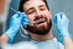 M??czyzna ma z?by egzamininuj?cych przy dentystami Zamyka w g?r? widok fotografia stock