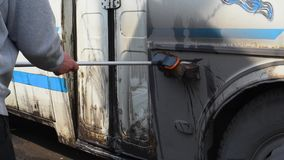 M??czyzna myje brudnego autobus na otwartej przestrzeni zbiory