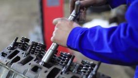 M??czyzna naprawia samochodowego silnika zbiory