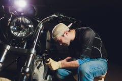M??czyzna naprawiania rower Ufny m?odego cz?owieka naprawiania motocykl blisko jego gara?u obraz stock