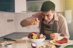 M??czyzna narz?dzania jedzenie W kuchni fotografia stock