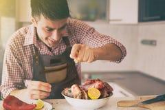 M??czyzna narz?dzania jedzenie W kuchni obraz royalty free