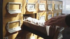M??czyzna otwiera baza danych kre?larza M?oda bibliotekarka otwiera bibliotecznego karcianego wska?nika Archiwum, baza danych, bi zdjęcie wideo