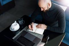 M??czyzna pisze w notatniku i pracuje z komputerem przy sto?em w sklepie z kaw? Freelancer pracuje na laptopie, pisze w notatniku zdjęcia royalty free