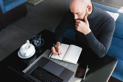 M??czyzna pisze w notatniku i pracuje z komputerem przy sto?em w sklepie z kaw? Freelancer pracuje na laptopie, pisze w notatniku obrazy stock