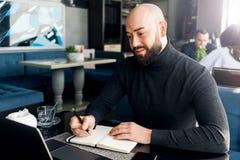 M??czyzna pisze w notatniku i pracuje z komputerem przy sto?em w sklepie z kaw? Freelancer pracuje na laptopie, pisze w notatniku obrazy royalty free