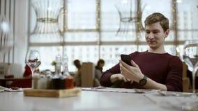 M??czyzna siedzi przy sto?em w restauracji, patrzeje na rachunku i robi zap?acie kart?, Kelner trzyma ?miertelnie w r?kach zdjęcie wideo