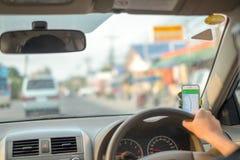 M??czyzna siedzi w samochodowej r?ce jedzie samoch?d na drodze otwiera GPS zastosowanie podróż jest przyglądający drogowego ruchu obraz stock