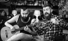 M??czyzna sztuki gitara w pubie Rozochoceni przyjaciele ?piewaj? pie?niow? gitary muzyk? Relaks w pubie Przyjaciele relaksuje w p obraz stock