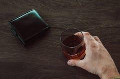 M??czyzna trzyma szk?o whisky Samiec wr?cza trzyma? szklan? fili?ank? z koniakiem Szkło z alkoholem i portfel jesteśmy na stole obraz royalty free