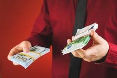 m??czyzna w czerwonej koszula z karty chwytami w jego r?ce zwitek rachunki na czerwonym tle fotografia stock