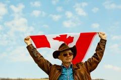 M??czyzna w kowbojskim kapeluszu bierze kanadyjczyk flag? zdjęcie stock
