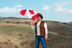 M??czyzna w kowbojskim kapeluszu bierze kanadyjczyk flag? obraz royalty free