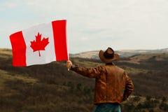 M??czyzna w kowbojskim kapeluszu bierze kanadyjczyk flag? zdjęcia royalty free