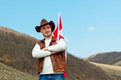 M??czyzna w kowbojskim kapeluszu bierze kanadyjczyk flag? zdjęcie royalty free