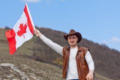 M??czyzna w kowbojskim kapeluszu bierze kanadyjczyk flag? fotografia royalty free