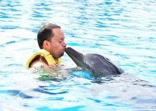 M??czyzny ca?owania delfin w basenie obraz royalty free
