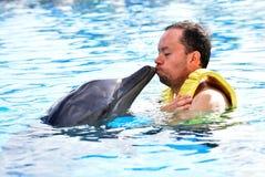 M??czyzny ca?owania delfin w basenie zdjęcia stock