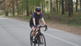 M?dchen auf dem schwarzen Fahrrad, das blaues Trikot und schwarzes Sturzhelmreiten im Park tr?gt Training f?r Radfahrenrennen Lan stock video footage