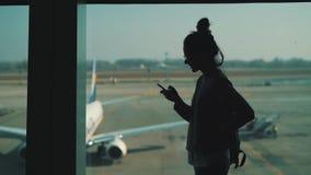 M?dchen benutzt Smartphone am Fenster im Flughafenabfertigungsgeb?ude stock video