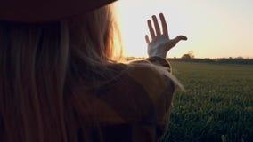 M?dchen betrachtet die Sonne durch ihre Hand Ein junges Mädchen mit einem Hut berührt die Strahlen der Sonne am Sonnenuntergang o stock video