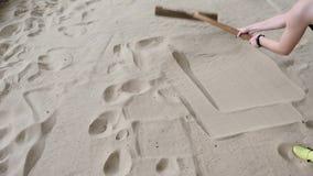 M?dchen, das den Sand nach einem Weitsprung im sandpit harkt