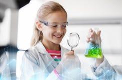 M?dchen, das in der Schule Labor des Reagenzglases studiert stockbild