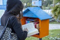 M?dchen, das ein Buch beschlie?t, um von einer kleinen Bibliothek f?r freies zu lesen stockfotografie