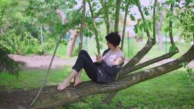M?dchen, das in einem Baum sitzt stock video footage
