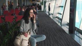 M?dchen, das an einem Handy im Flughafenaufenthaltsraum spricht stock video