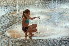 M?dchen an einem sonnigen warmen Tag, der drau?en in einem Wasserbrunnen spielt M?dchen gl?cklich im seichten Trinkwasser an des  lizenzfreie stockfotos