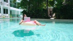 M?dchen im aufblasbaren Kreis im Pool mit einem Laptop, im Konzept des Freiberuflich t?tig seins und in der Erholung stock video