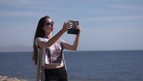 M?dchen macht selfie mit ihrem Telefon in der Zeitlupe auf dem Strand stock video