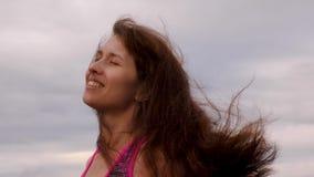 M?dchen mit dem Entwickeln des langen Haares l?chelt gegen bew?lkten Himmel Frau geht in wolkiges Wetter am Abend Nahaufnahme stock footage