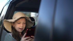 M?dchen mit dem Strohhut, der Social Media in einem intelligenten Telefon teilt Autoreise-Konzept stock video footage