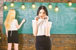M?dchen schaut w?hrend Damenschreiben auf dem Tafelhintergrund attraktiv, defocused Studenten- und Auszubildendkonzept kursteilne lizenzfreie stockfotografie