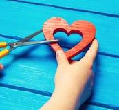 M?dchen schneidet das Herz mit Scheren, das Konzept des Brechens von Beziehungen, die Streite und Scheidung Verrat des othere bla lizenzfreie stockfotos
