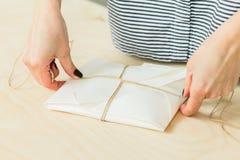 M?dchen verpackt ein Geschenk auf einem Holztisch lizenzfreie stockfotografie