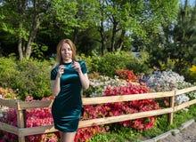 M?dchenblondine auf einem Hintergrund von Blumen im Park stockfotografie